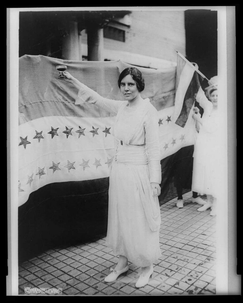 Alice Paul - full-length portrait - standing facing left raising glass with right hand - Library of Congress